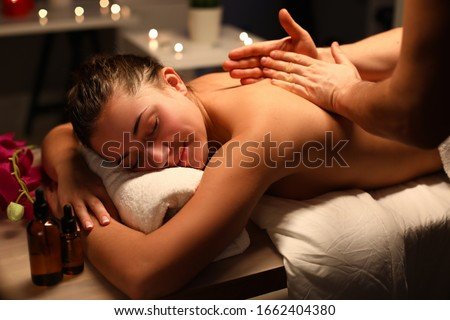 Young woman doing relaxing back massage in salon. Classic massage for purpose prevention. Anxiety disappears, tension is relieved. Lady in cozy atmosphere cabin to feel peace and quiet