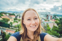 Young woman doing selfie on the background of the city of Dalat, Vietnam.