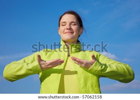 Young woman doing some breathing exercises outdoors