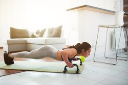 Young woman doing sport workout in room during quarantine. Fitness model stand in plank position using push up stand hand bar. Also pushing up on mat.