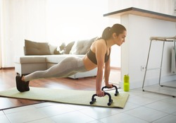 Young woman doing sport workout in room during quarantine. Picture of strong fitness model stand in plank position using push up stands hand bar. Exercising in room alone.
