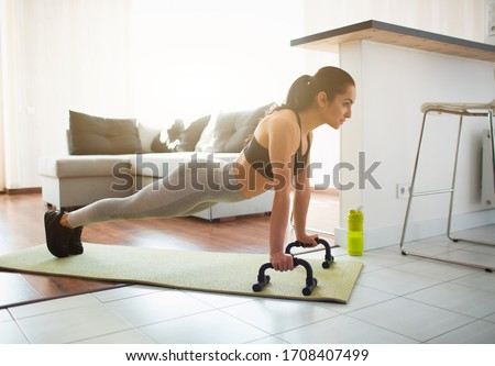 Photo of  Young woman doing sport workout in room during quarantine. Picture of strong fitness model stand in plank position using push up stands hand bar. Exercising in room alone.