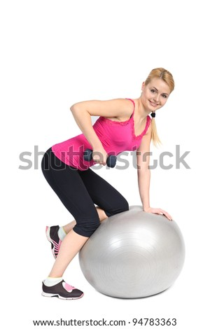 Young woman doing Standing Bent-Over Dumbbell Triceps Extension on Fitness Ball, phase 1 of 2.