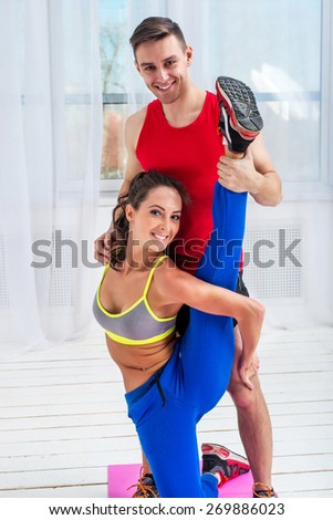 Young woman doing streching exercises with man smiling looking at camera concept training exercising workout fitness aerobic.