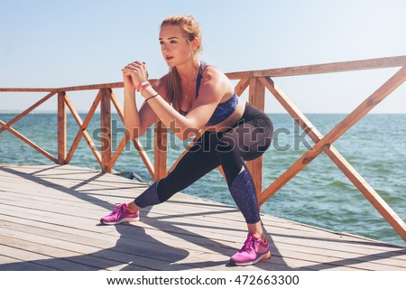 Young woman doing stretches after running workout. Active lifestyle. #472663300
