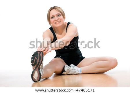 young woman doing stretching exercise at the gym
