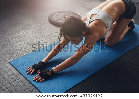 Young woman doing stretching exercises in a health club. Woman on fitness mat doing stretching workout at gym.