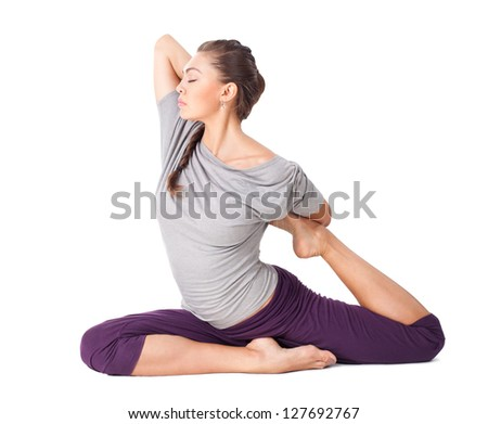 Young woman doing yoga asana Eka Pada Rajakapotasana (one legged king pigeon) isolated on white background