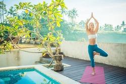 Young woman doing yoga asana in the morning near pool