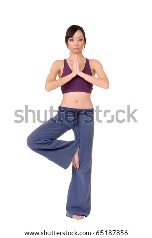 Young woman doing yoga excise by standing on one foot isolated over white.
