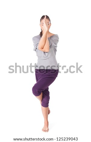 Young woman doing yoga exercise Garudasana eagle pose isolated on white background