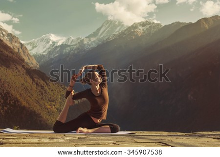 Young woman doing yoga exercise pigeon asana in beautiful mountains #345907538