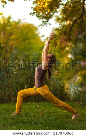 Young woman doing yoga exercises in the autumn city park.