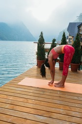 Young woman doing yoga exercises in the summer near lake. Health lifestyle