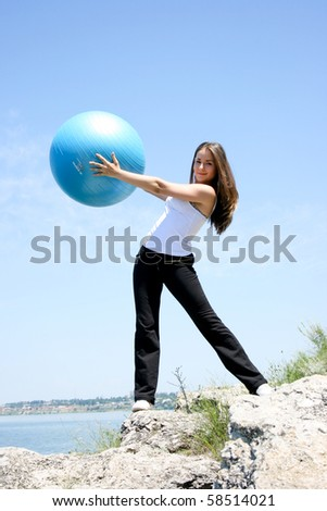 Young woman doing yoga exercises with the ball - stock photo