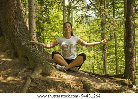 Young woman doing yoga in nature and sitting in lotus position near a tree in forest,breathing the clean air of mountains