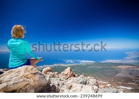 Young woman doing yoga meditation outside natural beautiful inspirational landscape environment, fitness and exercising motivation and inspiration in sunny mountains over blue sky and ocean sea.