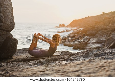 Young woman doing yoga on a rocky seashore