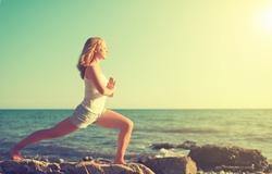 young woman  doing yoga on  coast of  sea on  beach