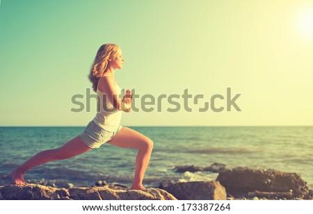 young woman  doing yoga on  coast of  sea on  beach ストックフォト ©