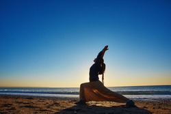 young woman doing yoga on the beach against sea and blue sky at early morning
