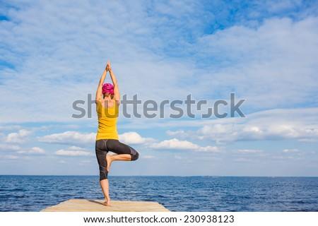 Young woman doing yoga pose under beautiful cloudy sky