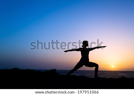 Young woman doing yoga pose warrior one, sunset silhouette in mountains. Sport and exercising in beautiful nature outdoors