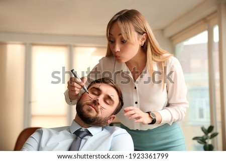 Young woman drawing on colleague's face while he sleeping in office. Funny joke