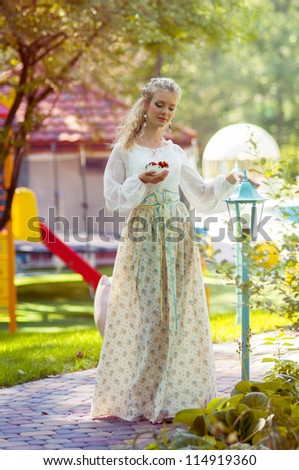Young woman dreams.  Woman holding a cup of tea with flower petals.