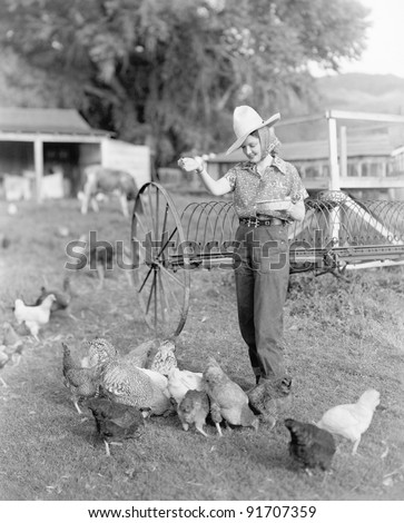 Young woman dressed as a farmer bringing food to the chicken
