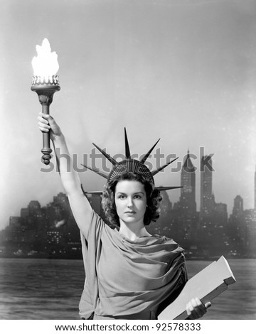 Young woman dressed as the Statue Of Liberty with skyscrapers in the background