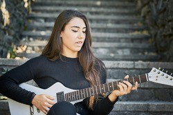young woman dressed in a sweater and black trousers and playing a white electric guitar sitting on a stone staircase