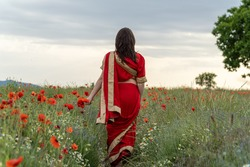 Young woman dressed in a traditional Indian costume called Sari walking in a red poppy flower field
