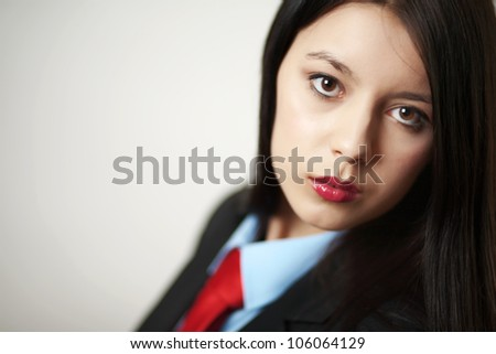 young woman dressed up in a man suit and tie looking at camera