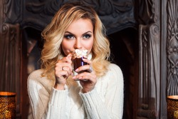Young woman dressed warmly, drinking hot chocolate sitting near fireplace