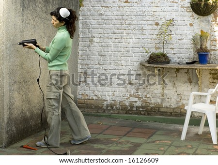 Young woman drills hole in wall. She is wearing a dust mask on her head. Horizontally framed photo.