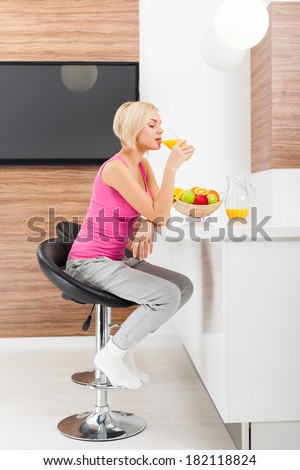 young woman drink orange juice glass in her kitchen at home indoors, pretty girl sitting a table female happy smile, natural organic fruit