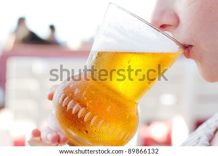 Young woman drinking a beer at the pub