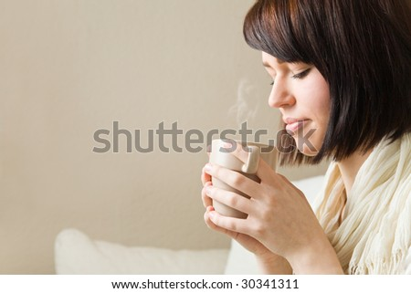 Young woman drinking a hot cup of coffee