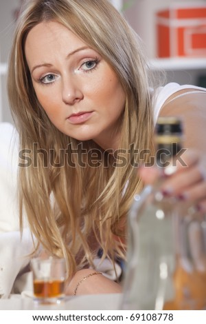 young woman drinking alcohol in depression at home