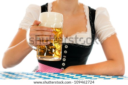 Young woman drinking beer in a bavarian dirndl