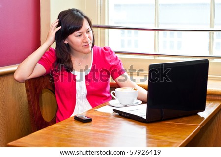young woman drinking cappuccino using her laptop in a cafe