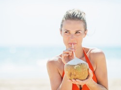 Young woman drinking coconut milk on beach and looking on copy space