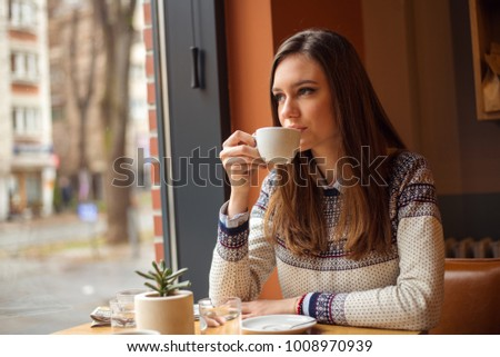 Young woman drinking coffe in cafe #1008970939