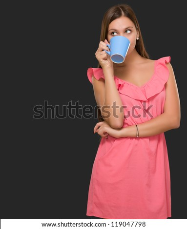 Young Woman Drinking Coffee against a black background