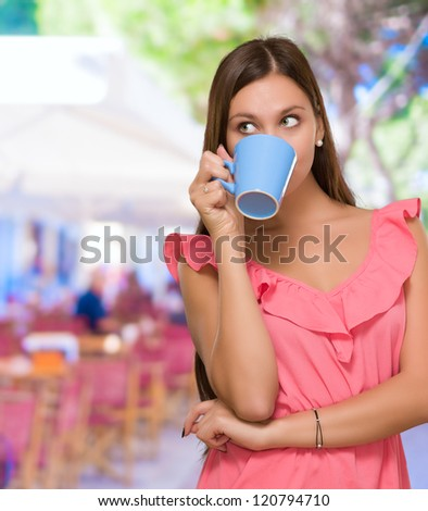 Young Woman Drinking Coffee at a restaurant