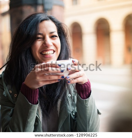Young woman drinking coffee in a cafe outdoors Shallow depth of field