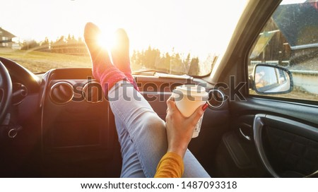 Young woman drinking coffee inside car in fall season - Girl relaxing and enjoying sunset traveling on europe mountains - Travel ,road trip and comfortable concept - Focus on paper hand Foto stock ©