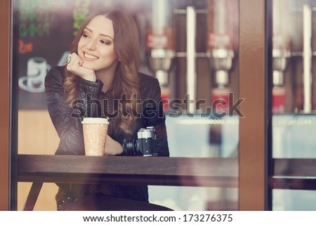 Young woman drinking coffee sitting indoor in urban cafe. Cafe city lifestyle. Casual portrait of teenager girl. Toned.