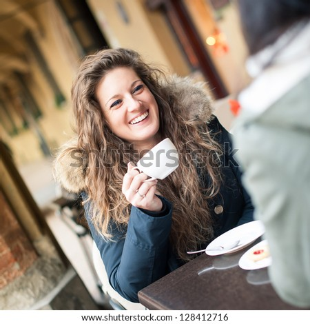 Young woman drinking coffee with friend in a cafe outdoors. Shallow depth of field.